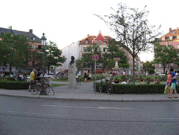 Der Gärtnerplatz München. Bepflanztes Rondell mit Radfahrern