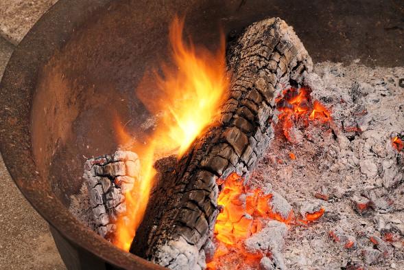 Grillschale mit brännendem Holzscheit und Asche